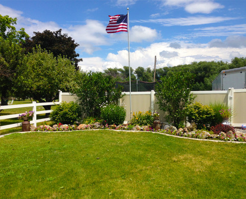 Two-Tone Vinyl Privacy Fence with Gate (on Right) Next to Flower Bed and Flag