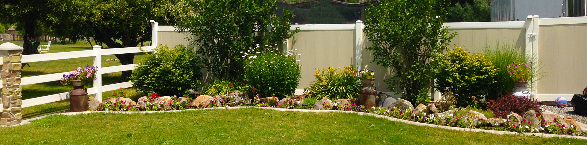 Two-Tone Vinyl Privacy Fence with Gate (on Right) Next to Flower Bed